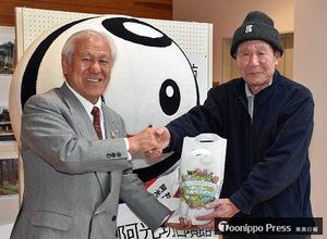三村町長(左)から記念品を贈られた、来館5千人目の川村さん