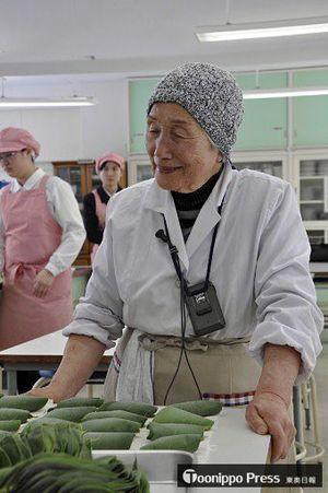 五所川原農林高校の生徒たちに笹餅の作り方を教えた桑田さん=17日午前