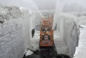 路上の雪を吹き飛ばしドッキングする青森側(手前)と十和田側(奥)の除雪車両=26日午前10時すぎ、傘松峠付近