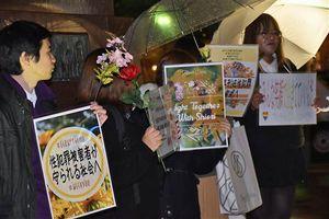 花とプラカードを掲げるフラワーデモの参加者たち=11日午後7時すぎ、弘前市のJR弘前駅前