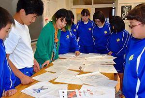 自分たちで描いたイラスト案を見ながら、豊川さん(左から3人目)と話し合う美術部の生徒たち