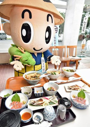 ひめます料理の一例を紹介する十和田湖PRキャラクター「南そボーヤ」