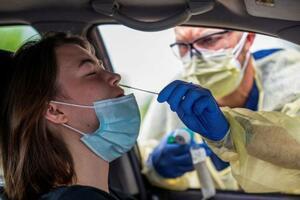 28日、米テキサス州で、新型コロナウイルスの検査を受ける女性(ロイター=共同)