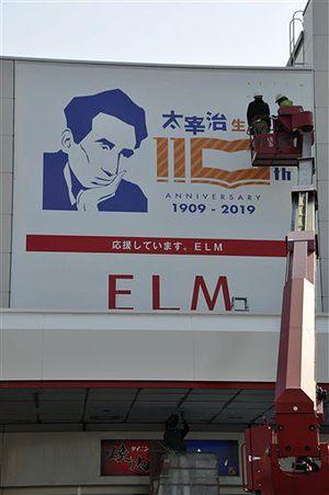 エルムの街ショッピングセンターの壁面に設置された「太宰治生誕110年」ロゴ看板