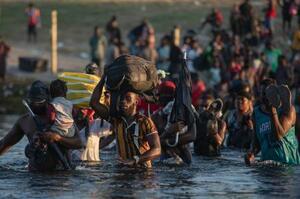 20日、米国とメキシコの国境沿いを流れるリオグランデ川を渡るハイチなどからの移民(AP=共同)