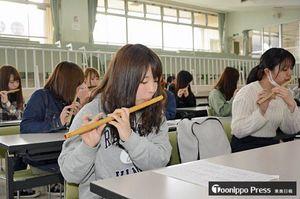 指使いやメロディーを確認しながら横笛でねぶたばやしの練習に取り組む学生たち