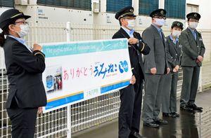 出発するリゾートうみねこに向けて「ありがとう」の幕を掲げる八戸駅員たち