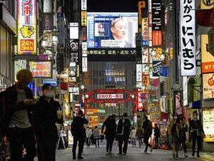 緊急事態宣言を月末まで延長し、4都府県に愛知、福岡両県を追加することを決め、記者会見する菅首相を映し出す大型ビジョン。手前は東京・新宿の歌舞伎町を行き交う人たち=5月7日午後
