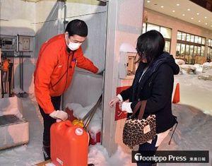 灯油が入ったポリタンクを店員(左)から受け取る市民=25日、青森市のホームセンター