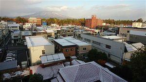 家々の屋根がうっすらと雪に覆われた弘前市内。奥に望む弘前公園の紅葉と雪の岩木山が季節の境目を思わせる=15日午前7時20分ごろ、同市鉄砲町、元寺町、下白銀町方面