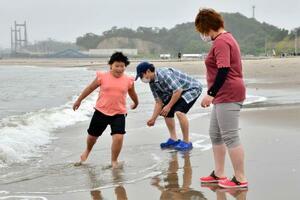 海開きした原釜尾浜海水浴場の波打ち際で遊ぶ親子連れ。両親はマスク姿だった=18日午前、福島県相馬市
