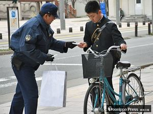 マナー向上を促すチラシの入ったポケットティッシュを受け取る自転車利用者