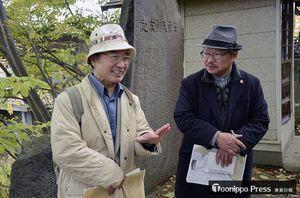 「十三の海鳴り」の取材旅行で青森県を訪れ、安藤氏ゆかりの地とされる藤崎八幡宮境内を見学する安部さん(右)。左は解説のため同行した弘大名誉教授の斉藤利男さん=2017年10月