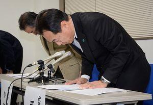 会見で運休の長期化を陳謝する青い森鉄道の千葉社長(手前)