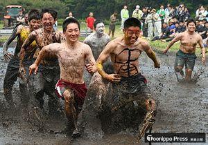一番で旗(手前)を取ろうと泥の中を全力で走る生徒たち=24日、三農