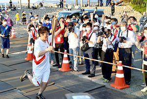 青森県で始まった聖火リレーで初日の最終走者を務め、笑顔で手を振るお笑いタレントの古坂大魔王さん=10日午後6時13分、青森市の青い海公園