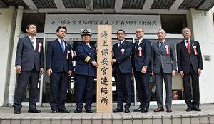 鯵ケ沢町役場に海上保安官連絡所の看板を設置する惣田部長(左から3人目)と平田町長(同4人目)ら自治体関係者