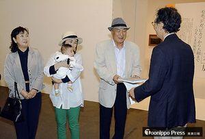 県立美術館の牧野館長特別補佐(右)から記念品を受け取る中村さん(右から2人目)と、一緒に訪れた(左から)すみ子さん、静花さん、千尋ちゃん