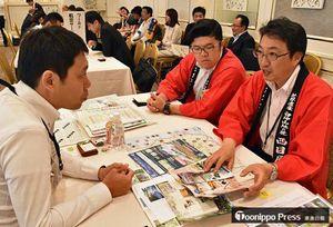 青森県側の参加者による宣伝に耳を傾ける、旅行会社の担当者(左)=4日、東京・西池袋