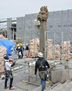 首里城の大龍柱の周辺に仮設の足場を設置する作業員=27日午前、那覇市