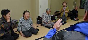 松尾町長(右)を前に、安堵の色を浮かべる避難所の町民=13日午前7時半、三戸町のアップルドーム