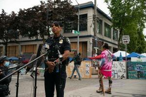 29日、米シアトルの銃撃事件現場の近くで記者会見するシアトルの警察幹部(ゲッティ=共同)