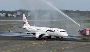 三沢空港に到着、消防車から放水アーチの歓迎を受ける羽田からの第2便=25日午後0時20分