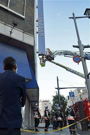 中三の看板の応急処置をする消防隊員ら=23日午後6時15分ごろ、青森市新町1丁目