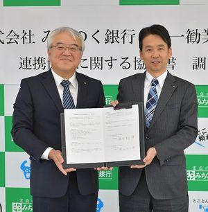 署名した協定書を手にする藤澤頭取(右)と新田理事長