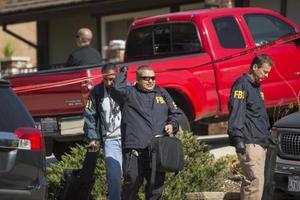 8日、銃乱射事件の容疑者の自宅を出る捜査員=米カリフォルニア州サウザンドオークス(ゲッティ=共同)