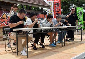 深浦、八峰両町のご当地グルメ早食い対決に挑戦する参加者