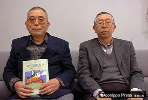 ガイドブックを手にする田名部編集委員長(左)と久保編集委員