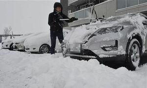自家用車に積もった雪を片付ける市民=21日午前8時5分、青森市西大野
