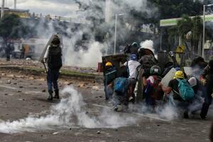 3日、コロンビア西部カリで、政府の税制改革法案に抗議して警官隊と衝突するデモ参加者ら(AP=共同)