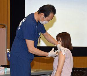 八戸市立市民病院の医療従事者を対象に始まった優先接種で、看護師にワクチンを接種する今院長(左)