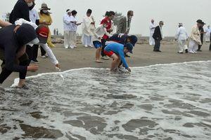 災いやけがれとともに人形を海に流す参加者