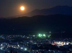 八甲田の裾野から昇る明るい満月=21日午後6時22分、青森市浪岡の西山公園展望台から