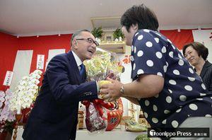 感謝の言葉を述べ、支持者から笑顔で花束を受け取る佐々木さん(左)=24日午後10時42分、五所川原市漆川の事務所
