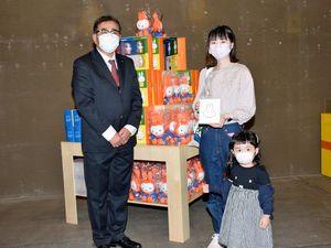 2万人目の入場者となり、橋本局長(左)から記念品を受け取った長谷川さんと娘の寧音ちゃん