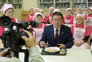 特別番組の収録で、五戸町食生活改善推進員会による健康メニューを試食する若宮町長(中)