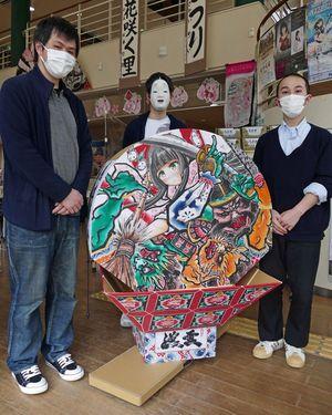 市まちなか情報センターに寄贈した小型ねぷたを囲む、田澤さん(左)と三浦さん(右)。中央のたやさんは、作中に登場する能面をかぶっている