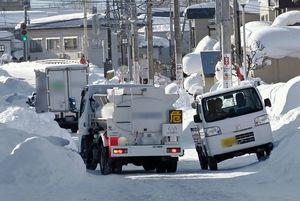 積雪で道幅が狭くなり、車体を傾けながらようやく擦れ違う車両=12日午後、青森市花園1丁目
