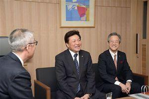 鎌田副市長(左)に喜びを報告する下山代表取締役社長(中)と板垣取締役副社長