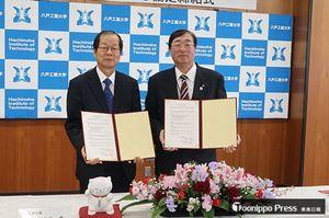 協定書を手にする長谷川学長(左)と日當会長