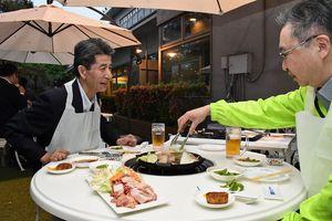 ホテルの日本庭園で、ビールを飲みながら肉料理を楽しむ来場者