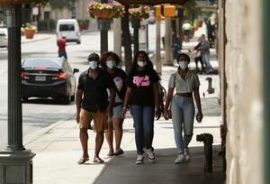 米テキサス州サンアントニオ中心部を、マスク姿で歩く人たち=7日(AP=共同)