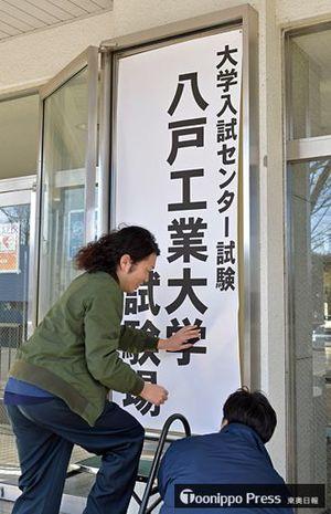 受験生の出入り口となる教養棟の玄関に案内の張り紙を掲示する職員=11日午前、八戸市の八戸工業大学