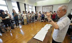 合唱指揮者として最後になる発表会に向けて団員たちを指導する小倉さん(右)=8日、青森市の古川市民センター