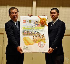 岩塚製菓の星野常務(左)から「五農米でつくった味しらべ」の発売記念パネルを受け取る秋田谷さん