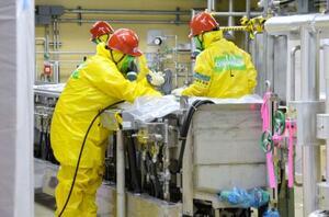 廃炉作業が始まった東京電力福島第2原発で、原子炉建屋の機器を除染する作業員=6日